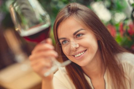 Photo for Smiling young girl tasting wine - Royalty Free Image