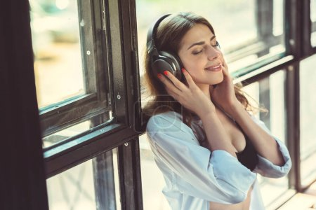 Young girl listening to music on headphones indoors