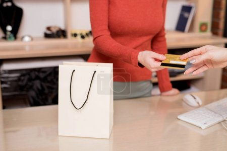 Young cashier with credit card in the store