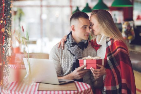 Photo for Young couple with a gift on a date - Royalty Free Image