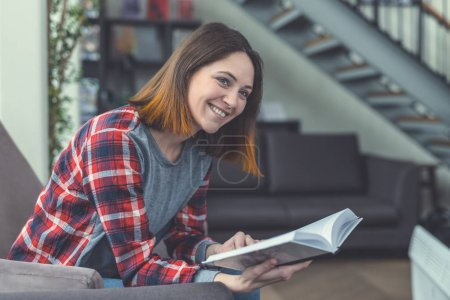 Photo for Smiling young girl with a book in the library - Royalty Free Image