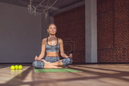 Photo for Young instructor doing yoga in the loft - Royalty Free Image