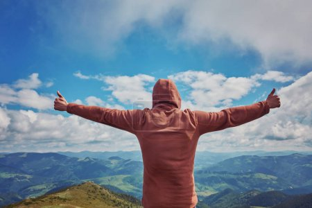 Photo for Happy tourist standing with backpack on a mountain top with raised up hands. Concept of success . Happy hiker winning reaching life goal, success, freedom and happiness, Thumbs-up - Royalty Free Image