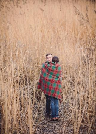 Photo for Young couple in love walking in the autumn park near the river. - Royalty Free Image