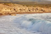 Beautiful wild beach with clear turquoise water and waves.