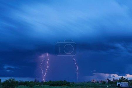 Foto de Masiva nube colorida tierra loco cielos rayos pernos golpear el horizonte de luces de la ciudad. - Imagen libre de derechos
