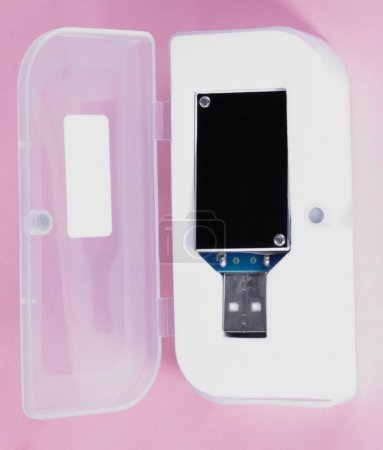 electronic device in plastic case on pink background at day