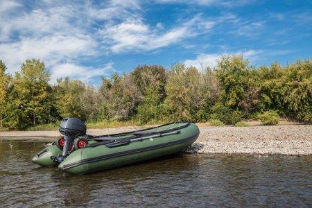 Photo pour Le bateau vert de pvc avec le moteur jet d'eau sur la rive de la rivière - image libre de droit