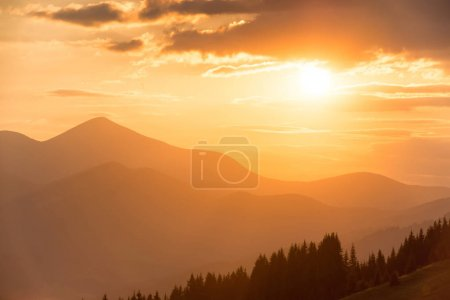 Photo for Beautiful dramatic sunset in the mountains. Landscape with sun shining through orange clouds - Royalty Free Image