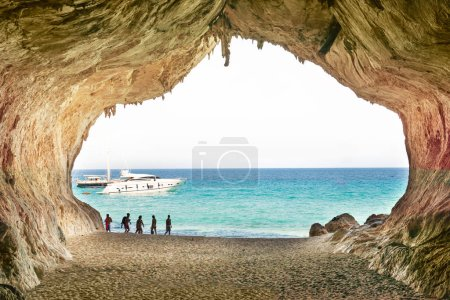 tourists walking near big cave