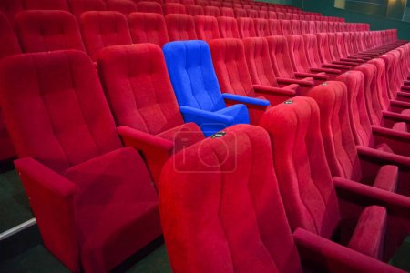Photo pour Chaise bleue entre les rangées de sièges rouges dans le théâtre modern. Scène de cinéma concept - image libre de droit