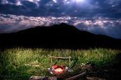 Campfire near mountain at night