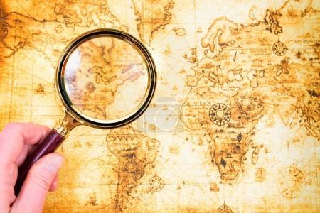 Photo pour Plan du vieux et exploré loupe dans une main. Fond de voyage Vintage - image libre de droit