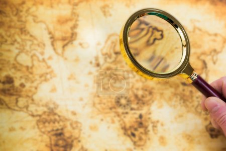 Old map and magnifying glass in a hand