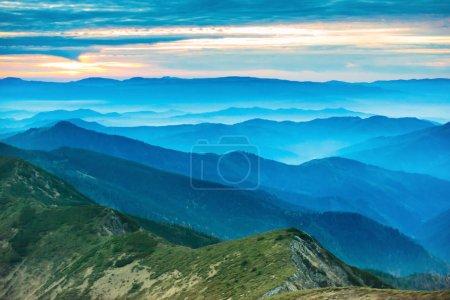Photo pour Coucher de soleil coloré en montagne. Nuages colorés dramatiques sur les collines bleues - image libre de droit