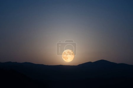 Photo for Moon rising on night sky with many stars above mountain range - Royalty Free Image
