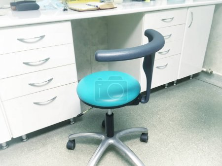 blue chair in doctor office near table
