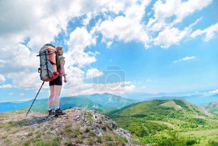 Femme de randonnée heureuse avec sac à dos au sommet de la montagne verte