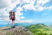 Happy hiking woman with backpack on top of green mountain