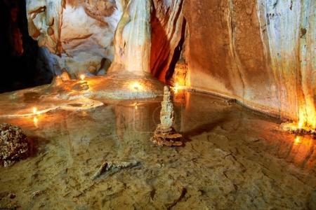Photo pour Cave intérieur foncé avec lac souterrain, lumière, stalactites et stalagmites - image libre de droit