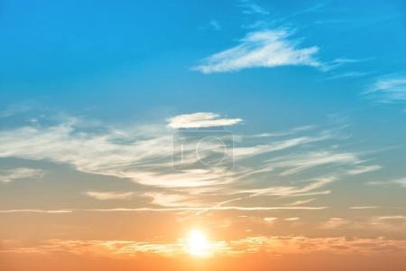 Foto de Puesta de sol cielo en azul y naranja con ventisca nubes y sol - Imagen libre de derechos