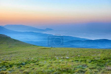 Photo for Sunset in mountains meadow with rocks and green grass - Royalty Free Image