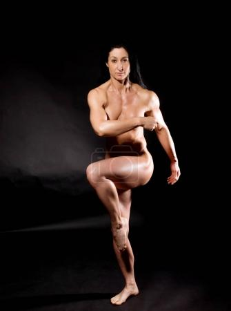 Photo for Muscular naked bodybuilder woman showing her muscles over black background. - Royalty Free Image