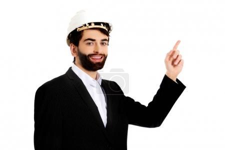 Photo pour Sourire beau homme d'affaires avec un casque à pointe vers le haut. - image libre de droit