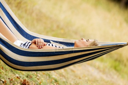 Photo for Young blonde woman resting on hammock. - Royalty Free Image