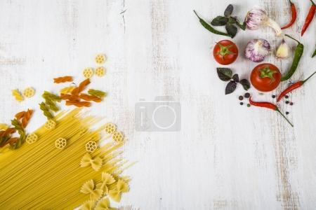 Raw pasta and spices in wooden table.