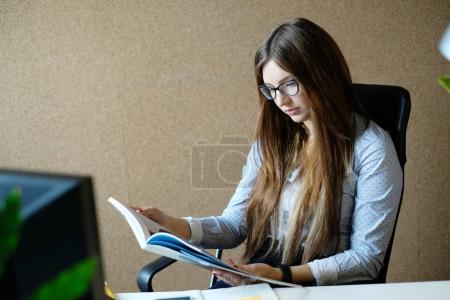 daily routine, young woman working with notebook in office