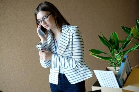 portrait of young attractive businesswoman talking over mobile phone in office