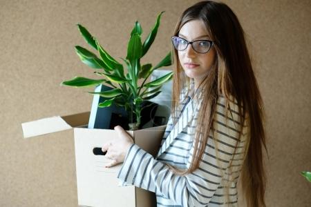 young woman being fired from work, holding box with pot plant and personal stuff