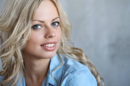 Photo for Beautiful young smiling woman posing in blue shirt - Royalty Free Image