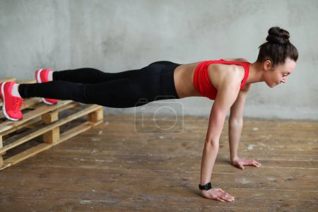 young sporty active woman stretching, fitness workout at home