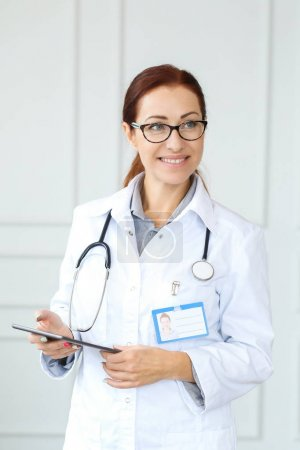 hospital and medicine concept, portrait of happy female doctor using tablet pc