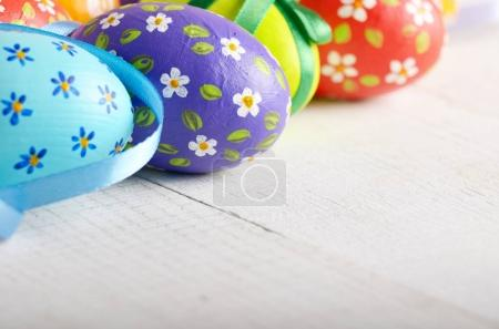 Closeup of rustic style painted easter eggs on white table