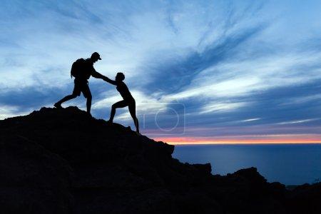 Photo pour Couple de travail d'équipe de randonnée, aider mutuellement, aide de confiance et silhouette dans les montagnes, coucher de soleil sur l'océan. Équipe d'alpinistes homme et femme, coup de main sur le sommet de la montagne, inspirational équipe escalade. - image libre de droit