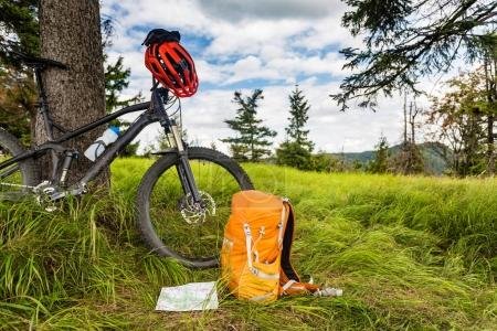 Photo for Mountain biking equipment in the woods, bikepacking adventure trip in green mountains. Travel campsite and MTB cycling with backpack, wilderness forest in Poland. - Royalty Free Image