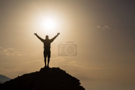 Photo for Man with arms outstretched celebrating or praying in beautiful inspiring sunrise with mountains and sea. Man hiking or climbing with hands up enjoy inspirational landscape on rocky top on Crete. - Royalty Free Image