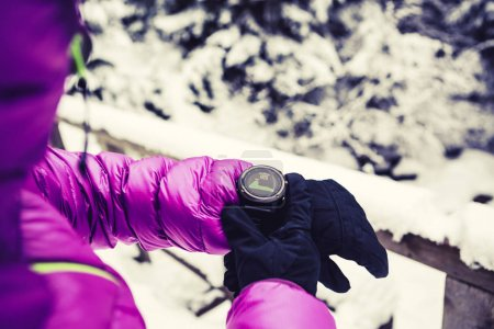 Photo for Woman hiker checking the elevation on sports watch, smartwatch with altimeter app in winter woods and mountains. Female trekker in white snowy forest trekking with electronics equipment technology. - Royalty Free Image