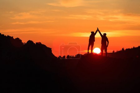 Photo for Teamwork couple celebrating silhouette in inspiring mountains sunset. Team of climbers celebrate reached goal and success. Achievement and motivation concept on top of mountain, Corsica France. - Royalty Free Image