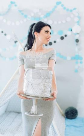 Photo for Pretty young mother in room with cake  in children room. - Royalty Free Image