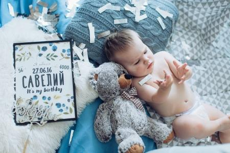 Adorable baby boy posing  with Teddy bear at home