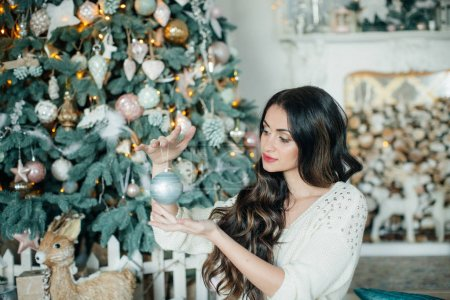 Beautiful woman in dress near Christmas tree posing at home