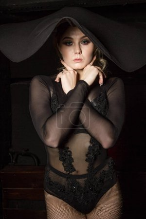 Photo pour Young girl in leather underwear and a hat with huge brim - image libre de droit