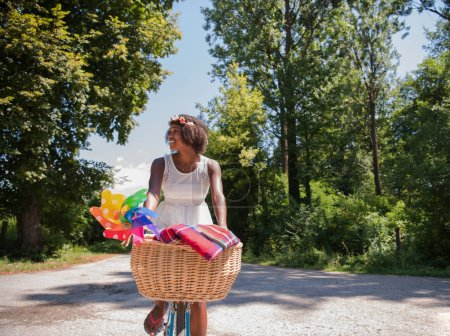 African american woman riding a bike in forest