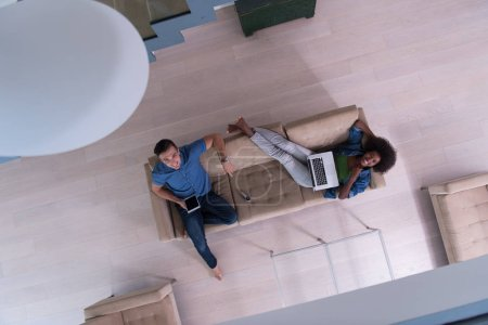 young multiethnic couple relaxes in the living room top view