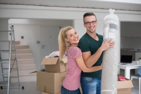 Couple carrying a carpet moving in to new home