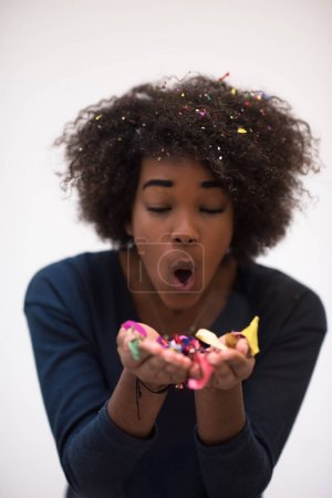 African American woman blowing confetti in the air